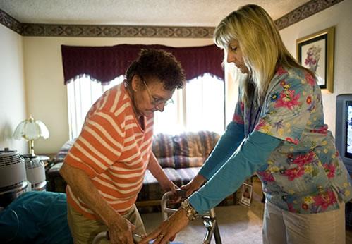 Caregiver helping an elderly woman balance her walker