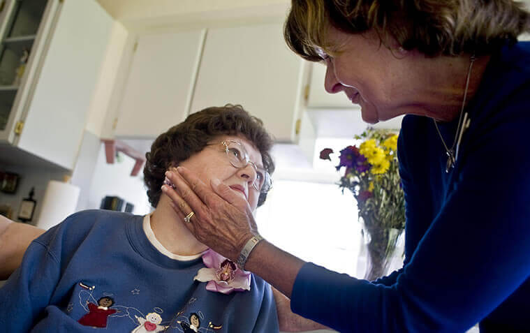 Caregiver checking an elderly woman's vitals
