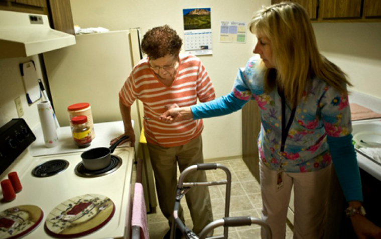 Caregiver helping elderly woman balance safely in the kitchen