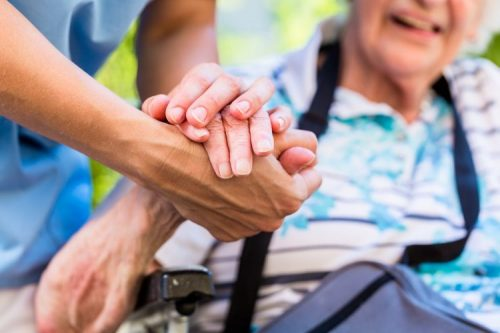 in home caregiver providing help with senior care holding an elder's hand