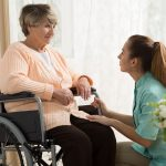 Caregiver helping a senior in a wheelchair with the activities of daily living
