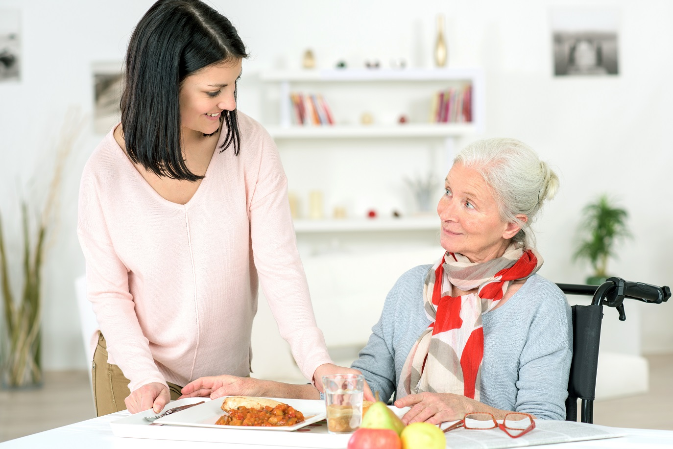 caregiver helping an elderly woman with meal preparation